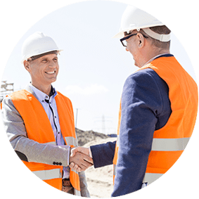 Two workers in safety vests and hard hats shaking hands